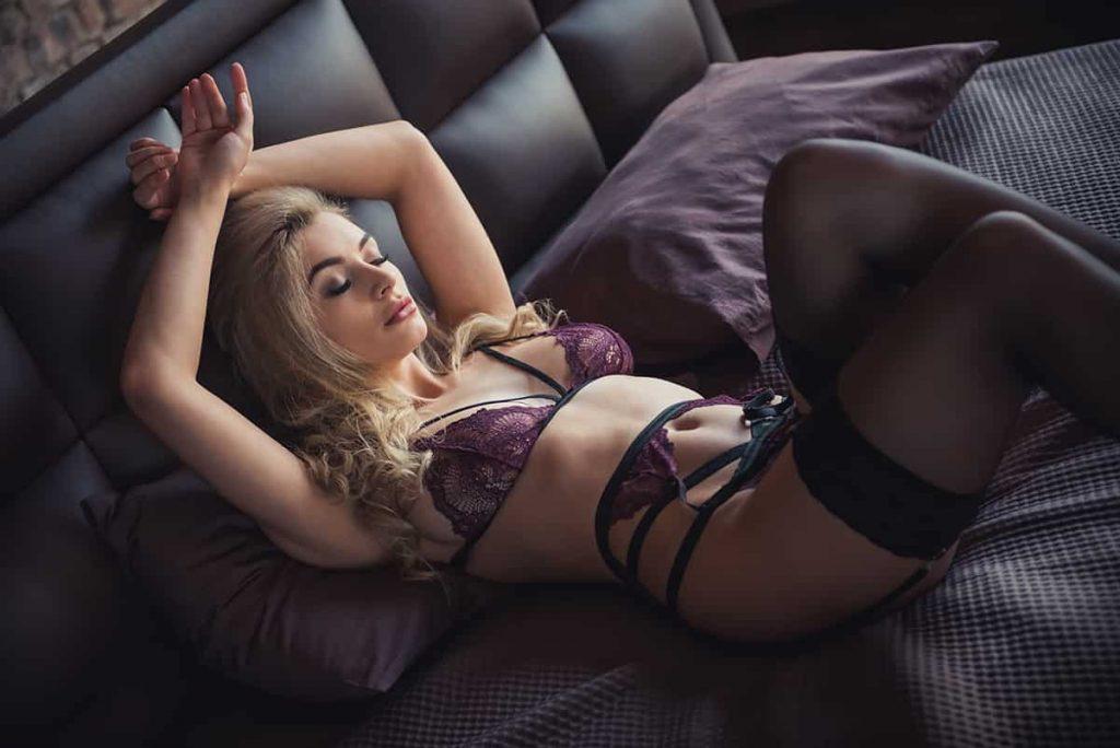 Séduisante femme allongée dans son lit dans sa lingerie.